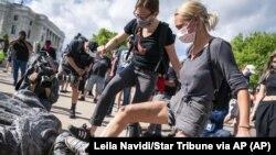 資料照片:在明尼蘇達州州議會前的哥倫布雕像被推到後,示威者用腳踩倒地的雕像。 (2020年6月10號,美聯社)