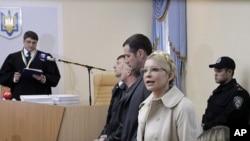 Former Ukrainian Prime Minister Yulia Tymoshenko speaks during her trial, with Judge, Rodion Kireyev, left, reading the indictment at the Pecherskiy District Court in Kiev, Ukraine, October 11, 2011.