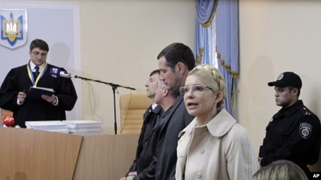 Former Ukrainian Prime Minister Yulia Tymoshenko speaks during her trial, with Judge, Rodion Kireyev, left, reading the indictment at the Pecherskiy District Court in Kiev, Ukraine, October 11, 2011.