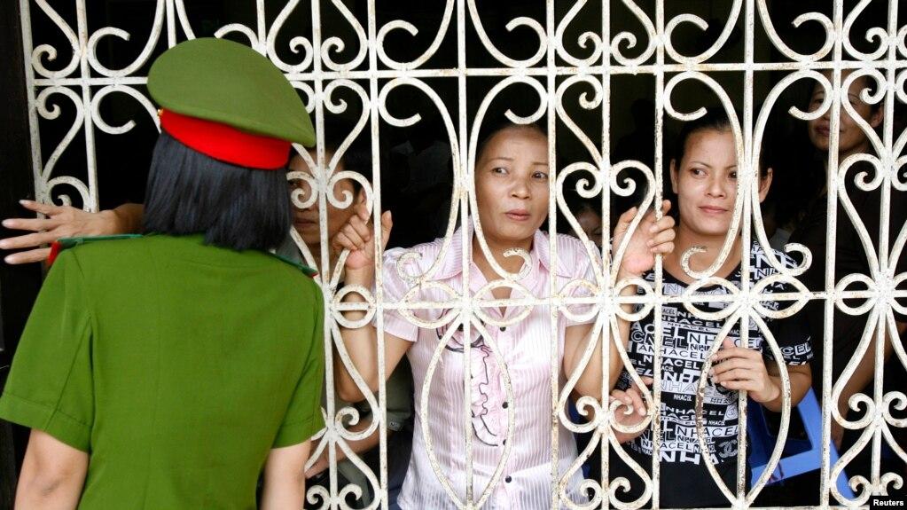 Công an Việt Nam đứng gác bên cạnh những người thân đến đón tù nhân từ nhà tù Thanh Xuân ở ngoại ô Hà Nội hôm 29/8/2010. Nhiều tổ chức trong và ngoài nước đang kêu gọi Thủ tướng Chính phủ Việt Nam thả tù nhân để ngăn chặn lây lan virus corona trong các nhà tù.