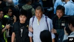 """香港壹传媒集团创办人黎智英2014年12月11日在香港政府总部外的""""占领区""""被警察带走。"""