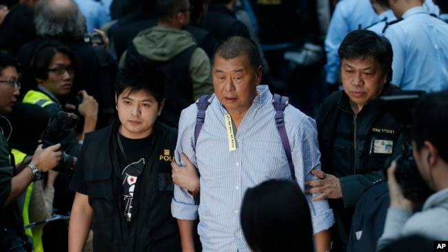 """香港壹传媒集团创办人黎智英2014年12月11日在香港政府总部外的""""占领区""""被警察带走。(资料照)"""
