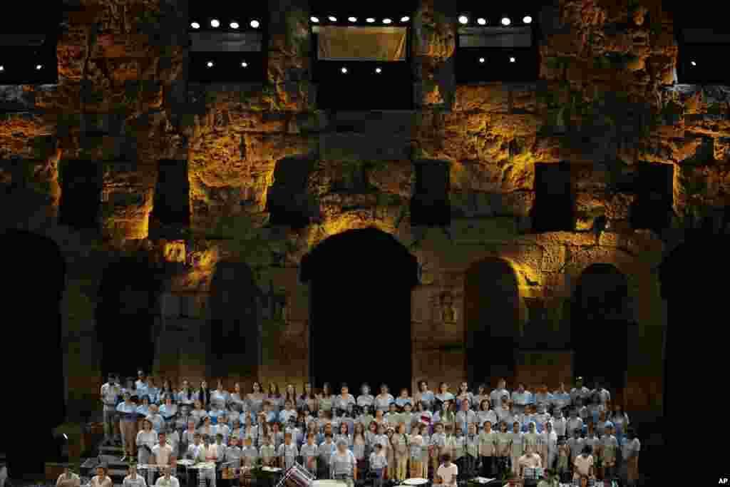 کودکان پناهنده و مهاجر در یک کنسرت در آتن یونان به صورت دسته جمعی آواز می خوانند.