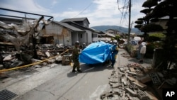 Les secouristes portent une victime de 93 ans du séisme, Yumiko Yamauchi, recouverte d'une feuille de plastique bleu, sur une civière au milieu des gravats d'une maison écroulée en Mashiki, dans la préfecture de Kumamoto, le sud du Japon, 16 avril 2016.