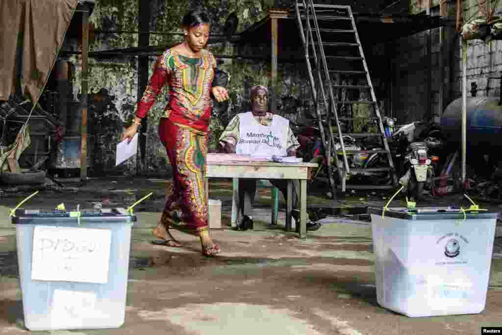A voter prepares to cast her ballot at a polling station in the Madina neighborhood of Conakry, Guinea, Sept. 28, 2013.