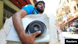 Qassem Istanbouli holds a film negative, in Tripoli, Lebanon, July 5, 2017. Istanbouli is restoring old cinemas into cultural centers.