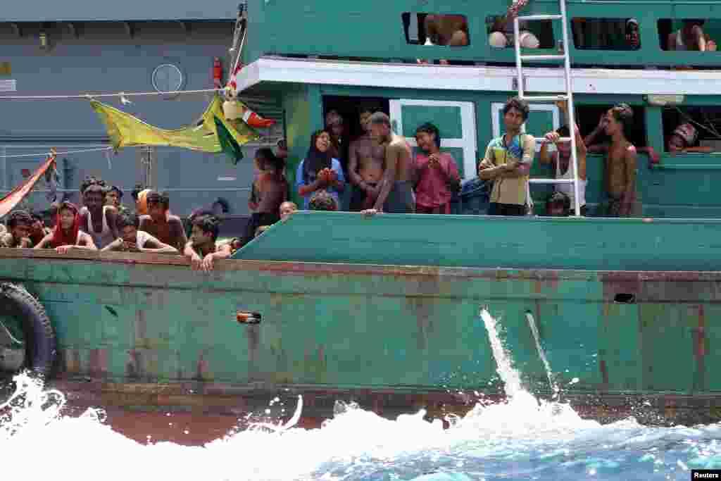 Beberapa migran putus asa setelah angkatan laut Thailand menghalau kapal mereka dari negara itu, di perairan dekat pulau Koh Lipe (16/5). (Reuters/Aubrey Belford)