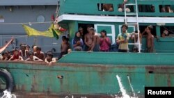 Some migrants despair after the Thai navy tows their boat away from Thailand, in waters near Koh Lipe island, May 16, 2015.
