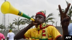 Un supporter du Mali gesticule et souffle une corne de vuvuzela à l'arrivée de l'équipe du Mali à l'aéroport de Malabo, avant le tournoi de football de la Coupe d'Afrique des nations 2015, le 16 janvier 2015,.