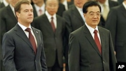 Russian President Dmitry Medvedev, left, with his Chinese counterpart Hu Jintao arrives for a welcoming ceremony at the Great Hall of the People in Beijing, 27 Sept. 2010