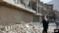 Seorang pemberontak Houthi tampak berjalan di tengah reruntuhan yang tersisa dari serangan udara pimpinan Saudi. Sana'a, Yaman.
