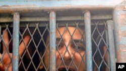 Egyptian blogger and former law student Abdel Karim Suleiman, also known as Kareem Amer, looking out of a police bus after his trial in the port city of Alexandria, 100 kms north of Cairo, (File).
