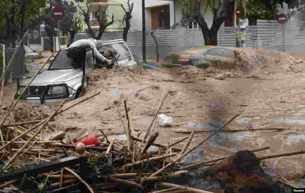 Người đàn ông trong quận Chalandri phía bắc thủ đô Athens của Hy Lạp cố gắng cứu một phụ nữ lái chiếc xe bị kẹt trong nước lũ.