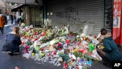 Flowers and candles are placed in front of the restaurant on Rue de Charonne, Paris, Nov. 15, 2015, where attacks took place on Friday.