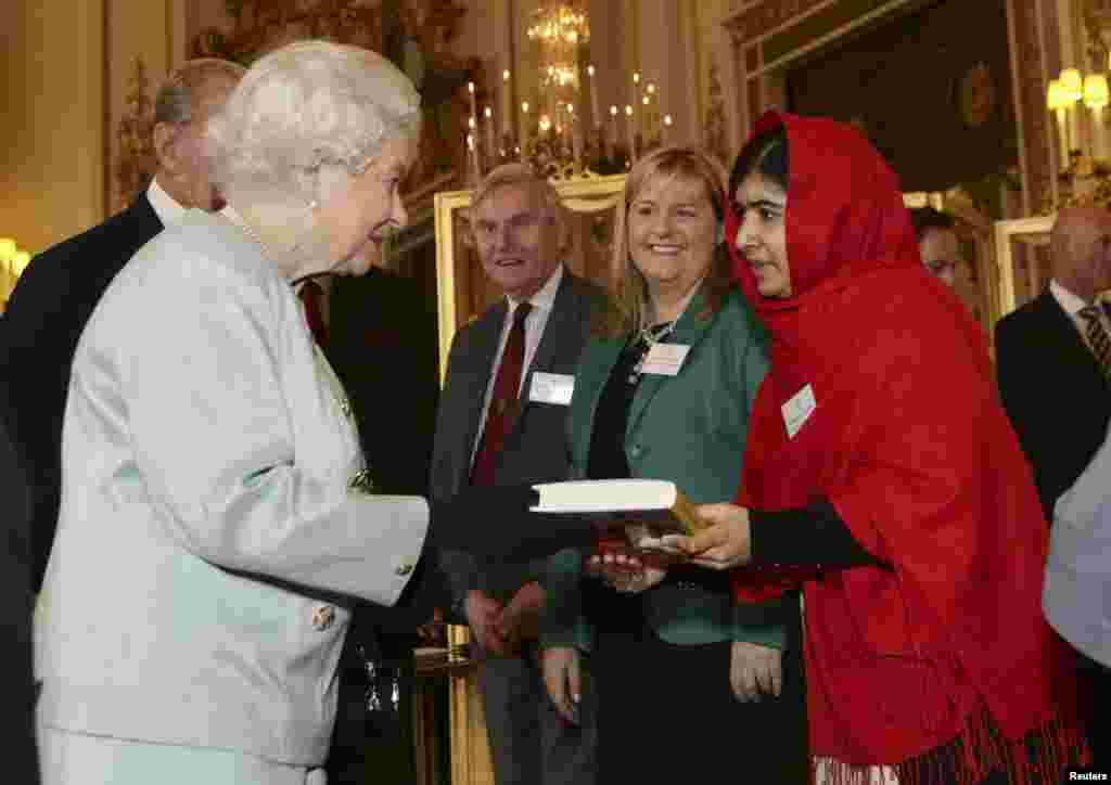 "Pakistani teenage activist Malala Yousafzai gives a copy of her book ""I am Malala"", to Britain's Queen Elizabeth during a Reception for youth, education and the Commonwealth at Buckingham Palace in London."