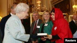 "Malala Yousafzai gives a copy of her book ""I am Malala"", to Britain's Queen Elizabeth during a Reception for youth, education and the Commonwealth at Buckingham Palace in London October 18, 2013."
