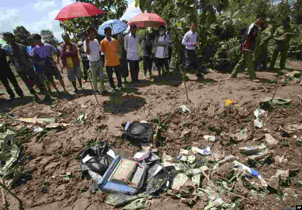 People look at the debris of a Lao Airlines turboprop plane that crashed into the Mekong River, in Pakse, Laos, Oct. 17, 2013.