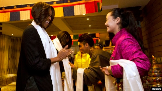 U.S. First Lady Michelle Obama, her daughters Sasha, Malia, and mother Marian Robinson are greeted with a Khata scarf by Tibetan students as they arrive to a Tibetan restaurant for lunch in Chengdu in southwest China's Sichuan province, March 26, 2014.