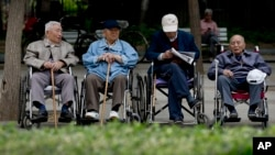 In this 2013 file photo, a group of elderly men take a rest on their wheelchairs at a park in Beijing. China passed law requiring people to visit or keep in touch with their elderly parents. (AP Photo/Andy Wong)