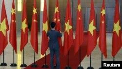 Một nhân viên chỉnh cờ Trung Quốc trước khi Chủ tịch Trung Quốc Tập Cận Bình tới Quốc hội Việt Nam tháng 11 năm 2015. (Ảnh minh họa).