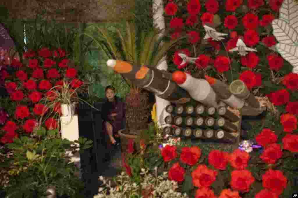 24일 정전 60주년 기념하는 평양의 행사장에 김일성.김정일을 기리는 꽃과 모형 미사일이 전시되어 있다.