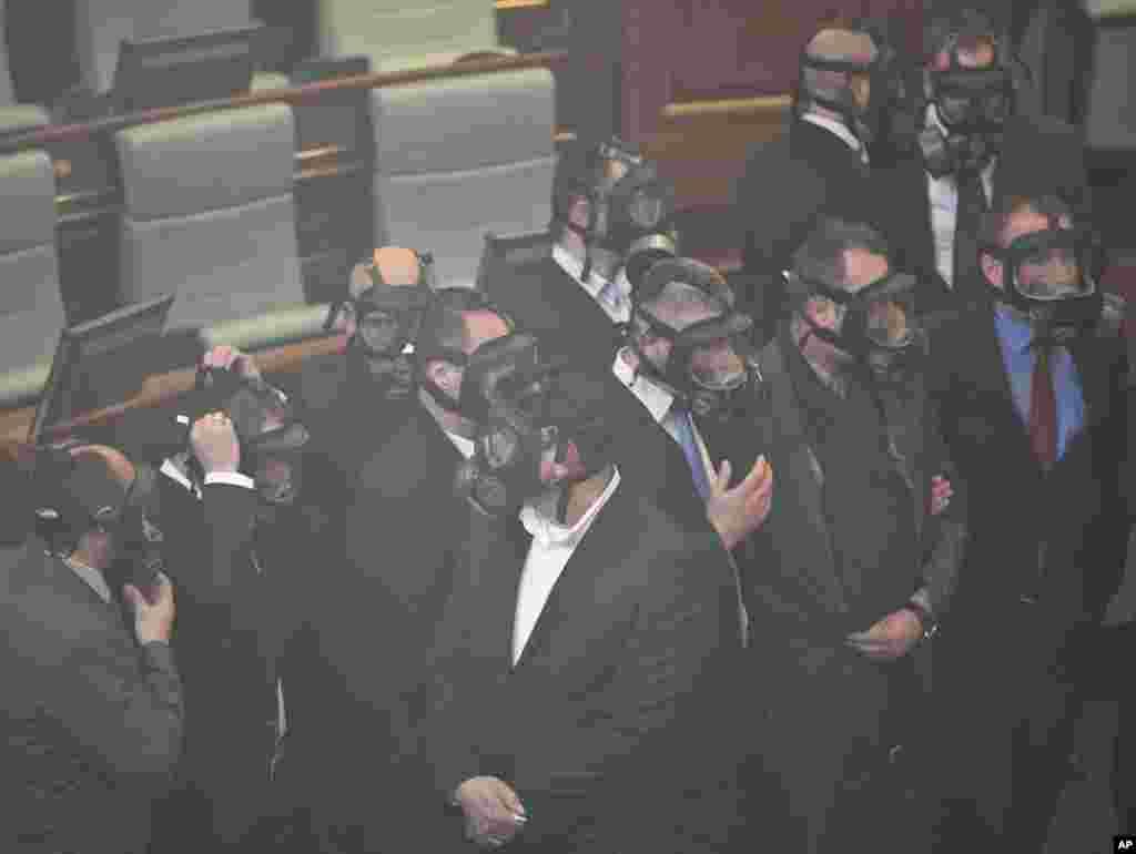 مسئولان امنیت مجلس نماینده گان کوزوو بعد از پاشید گاز اشک آور از سوی یکی از نماینده گان مجلس ماسک پوشید اند
