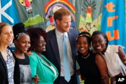 Britain's Prince Harry was among other famous people who spoke at the conference, 2016. He is pictured with young AIDS Ambassadors. (AP Photo)