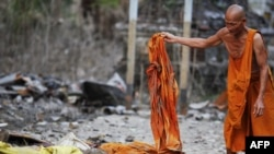 Một tu sĩ Phật giáo nhặt lại một chiếc áo choàng sau khi nước lũ rút đi ở Ayutthaya, Thái Lan