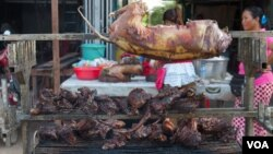 Grilled dog meat are on display at a food kiosk along a street in Phnom Penh. (Neou Vannarin/VOA Khmer)