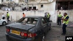 Binh sĩ và nhân viên cấp cứu Israel kiểm tra hư hại một chiếc xe sau khi một tên lửa được phóng sang từ dải Gaza 22/8/2014.