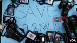 Solidaritas Wartawan Bandung melakukan unjuk rasa dengan melepas atribut jurnalis mereka, 15 November 2014 (Foto: VOA/Teja Wulan)