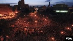 Ribuan demonstran anti-pemerintah terlihat berkumpul malam hari di Tahrir Square Kairo, Mesir, Selasa (2/1).