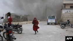 지난 5월 시리아 이들리브주 파르 루마에서 시리아 여성이 정부군의 공습을 피해 달리고 있다.