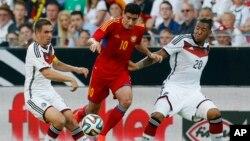 Joueur de l'équipe allemande, Jerome Boateng, à droite, et son co-équipier, Philipp Lahm, à gauche, se discutent une balle avec Gevorg Chazaryan de l'Arménie, au centre, lors d'un match amical de football entre l'Allemagne et l'Arménie dans l'arène Coface à Mayence, Allemagne, 6 juin, 2014. (AP Photo / Michael Probst)