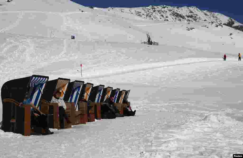 Warga duduk di kursi pantai menikmati sinar matahari di pegunungan Muottas Muragle, pada ketinggian 2546 meter, di kota resor St. Moritz, Swiss.
