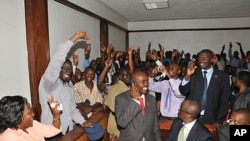 Uganda's top opposition leader Kizza Besigye, second left (A4C participant), waves to supporters inside the court in Kampala, Uganda after he was freed on bail, March 28, 2012.