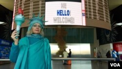 "Lindley Hanlon, a film professor at CUNY, spent Monday afternoon at JFK International Airport to welcome refugees. ""I'm trying to welcome people to our shores, as I've always done for 131 years,"" she said, referring to Lady Liberty's arrival in New York harbor in June of 1885. (Ramon Taylor/VOA)"