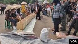 Warga menyaksikan unjukrasa sembilan perempuan asal Pegunungan Kendeng, Jawa Tengah di depan Istana Negara, Jakarta, Selasa sore 12/4 (VOA/Fathiyah).