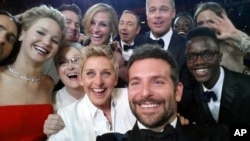 This image released by Ellen DeGeneres shows actors front row from left, Jared Leto, Jennifer Lawrence, Meryl Streep, Ellen DeGeneres, Bradley Cooper, Peter Nyong'o Jr., and, second row, from left, Channing Tatum, Julia Roberts, Kevin Spacey, Brad Pitt, L