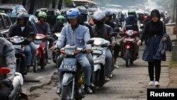Seorang perempuan berjalan di trotoar, dilewati puluhan sepeda motor di Jakarta Selatan.