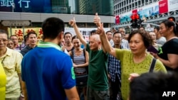 People react to pro-democracy protests in Hong Kong's Mongkok district, Oct. 11, 2014.