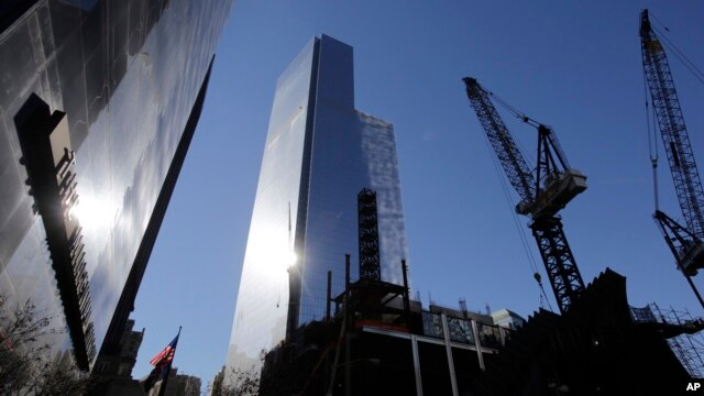 4 World Trade Center, center, towers over construction cranes at the trade center site, Nov. 13, 2013, in New York City