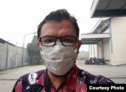 Arif Rahman Hakim, warga Pekanbaru yang harus bekerja dengan mengenakan masker. (Foto: Arif RH)