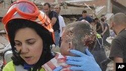 یکتن از افراد گروه نجات در هسپانیه طفلی را که در اثر زلزله جراحت برداشته از زیر آوار خاک بیرون کشیده است.