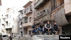 Tentara Pembebasan Suriah berpose di atas sebuah tank yang mereka sita dari rejim Suriah di Homas, awal April 2013. Kota ini kembali dikuasai oleh Pasukan Pemerintah Suriah, Kamis (2/5).