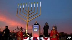 El jefe de personal de la Casa Blanca, Denis McDonough, junto al rabino Levi Shemtov hablaron durante la iluminación de la menora nacional en Washington, en el Ellipse, el domingo, 6 de diciembre de 2015.