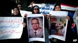 """Muslim Brotherhood supporter carries a banner, center, in Arabic that reads, """"freedom to doctor Mohammed Abdel Monem, arrested in the United Arab Emirates,"""" during an ongoing protest in front of the United Arab Emirates embassy, unseen, in Cairo, Egypt, J"""