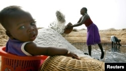 FILE - Mariama Diokh throws salt onto a pile while her 5-month-old infant sits nearby on the Senegal coast close to the Gambian border, June 2006.