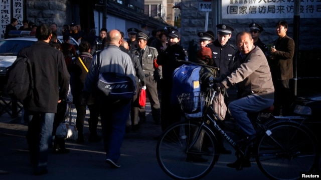 A man cycles past security personnel, and uniformed and plainclothes police, who are standing outside the entrance to a government building where petitioners congregate daily to protest private equity scams, in central Beijing, October 22, 2012.