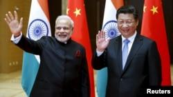 14일 중국 산시성에 도착해 시진핑 중국 국가 주석(오른쪽)의 영접을 받은 나렌드라 모디 인도 총리가 기자단을 향해 손을 흔들고 있다.